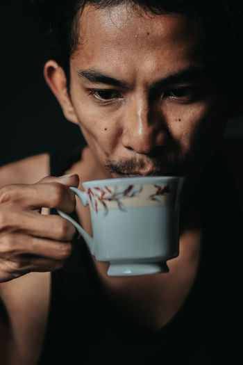 Close-up portrait of woman holding coffee cup