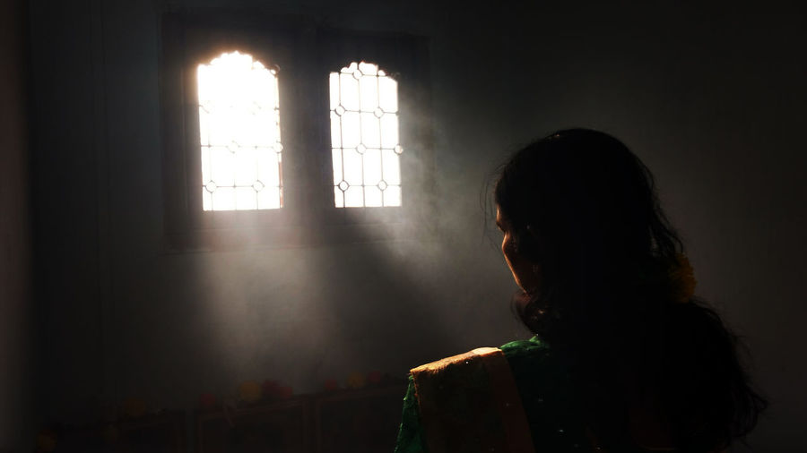 Rear view of woman praying against window in room