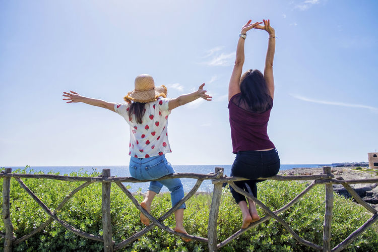 Rear view of two young woman sitting on a fence with arms raised against blue sky Sky Leisure Activity Real People Casual Clothing Nature Two People Human Arm Full Length Togetherness Lifestyles Day Emotion Women Rear View Arms Raised Bonding Positive Emotion Adult People Men Outdoors