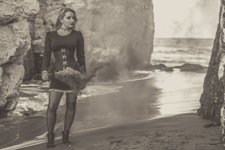 Portrait of young woman standing on rock at beach