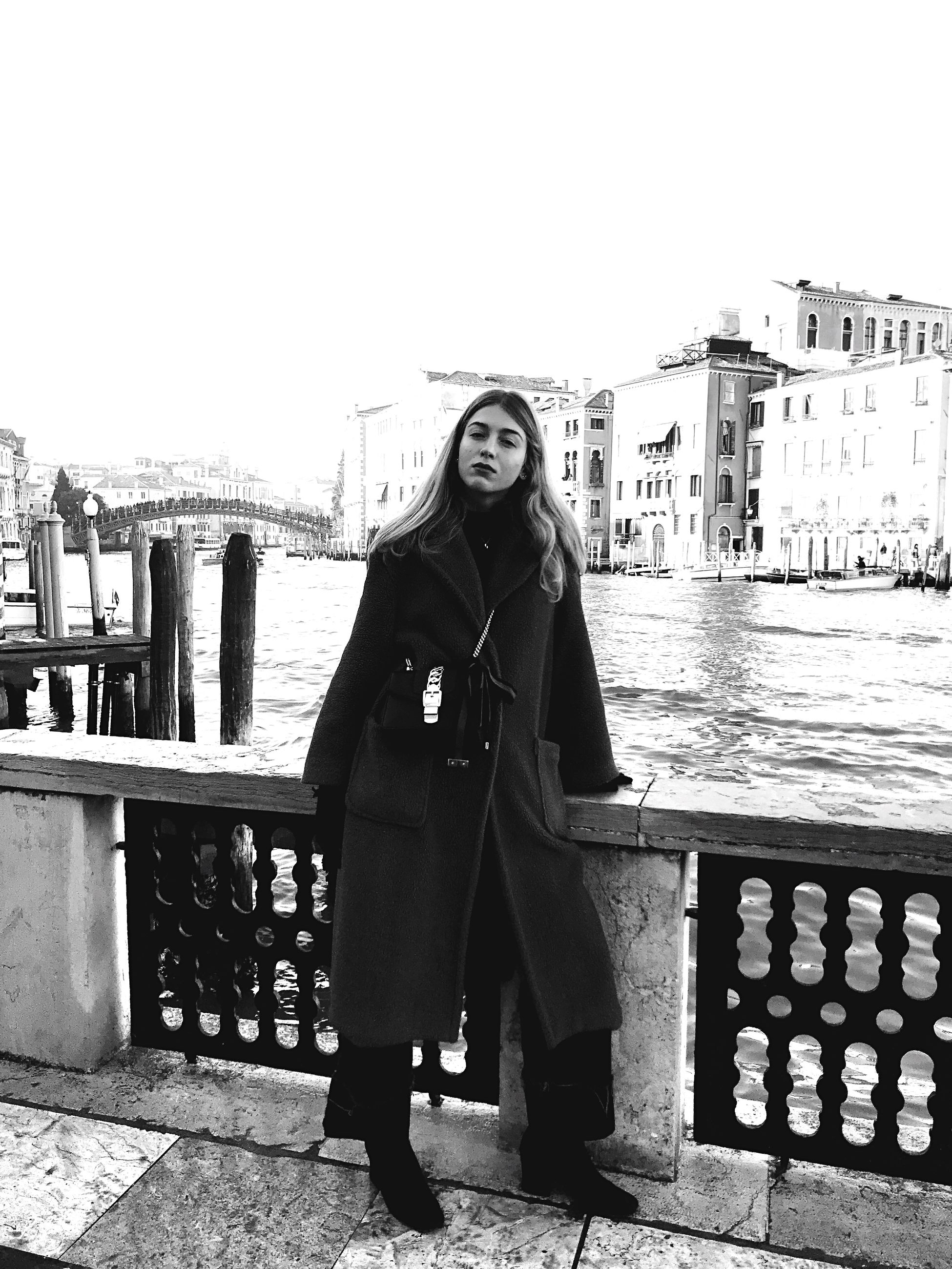 architecture, built structure, building exterior, water, one person, looking at camera, portrait, real people, railing, lifestyles, standing, leisure activity, young women, nature, front view, full length, river, women, outdoors, warm clothing, beautiful woman