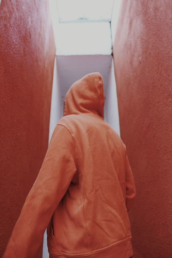Midsection of man standing against red wall