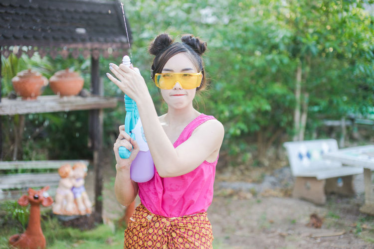 Portrait Of Young Woman Holding Squirt Gun While Standing In Yard