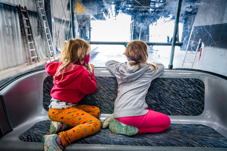 Rear view of girls looking through window while sitting on vehicle seat
