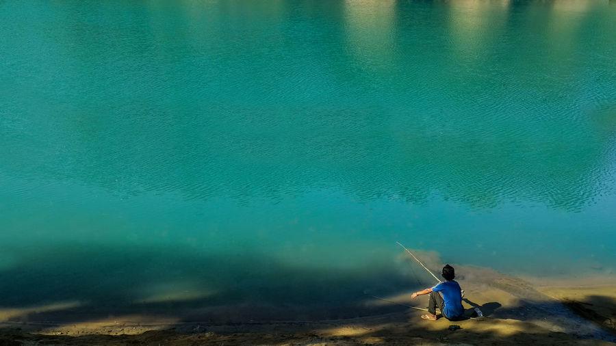 Boy sitting by lake