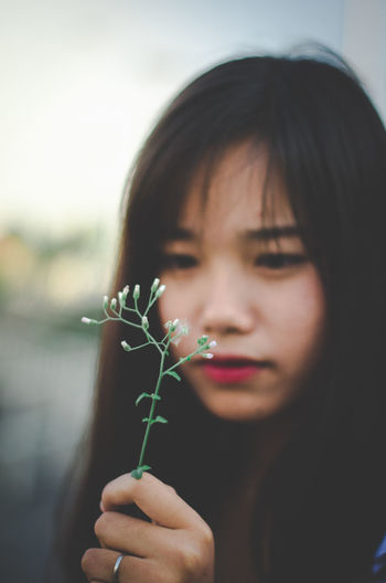 Close-up of beautiful woman holding plant
