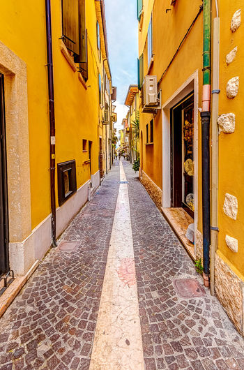 A narrow street Architecture Building Exterior Built Structure Calm City Day Direction Empty Italian Italy LINE Narrow No People Outdoors Quiet Sky Street Summer The Way Forward Tight Vanishing Point Warm Yellow Yellow Flower