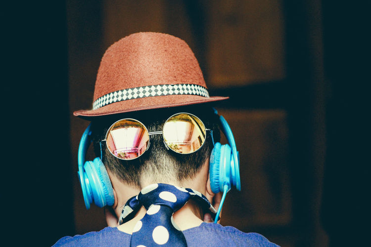 Rear view of boy wearing sunglasses and hat while listening to music