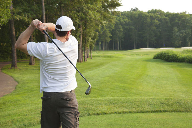 Rear view of man playing golf at field