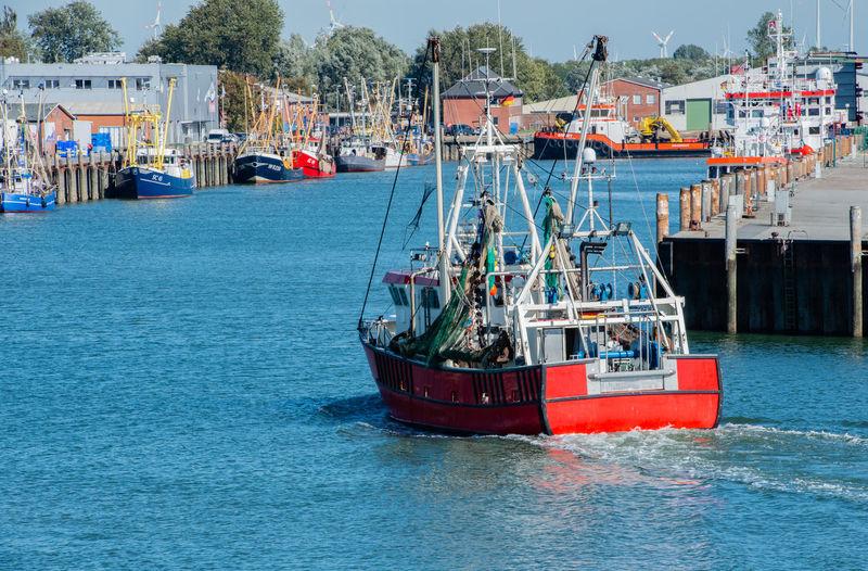 Fishing boat sailing on sea at harbor