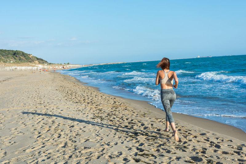 Woman Running At Beach Against Sky