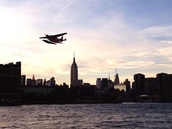 Airplane Flying Over River In City