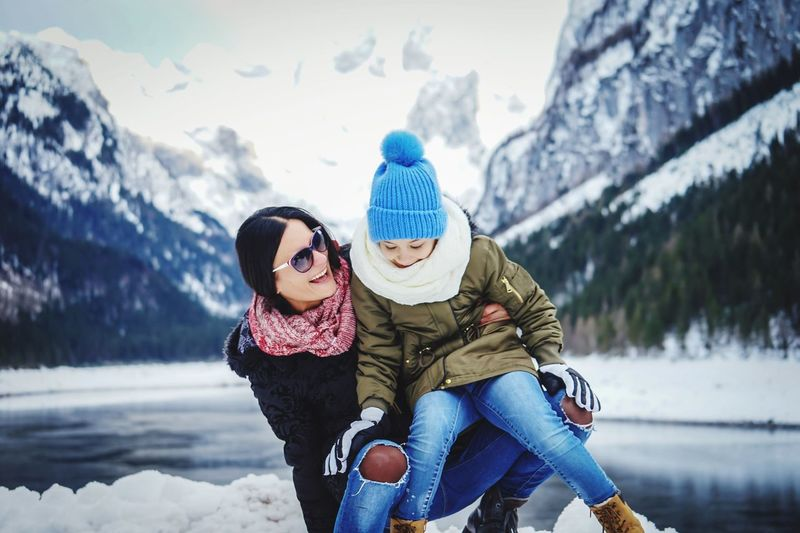 Smiling Mother With Daughter On Snow During Winter