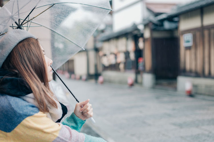 Midsection of woman sitting holding umbrella on street in city