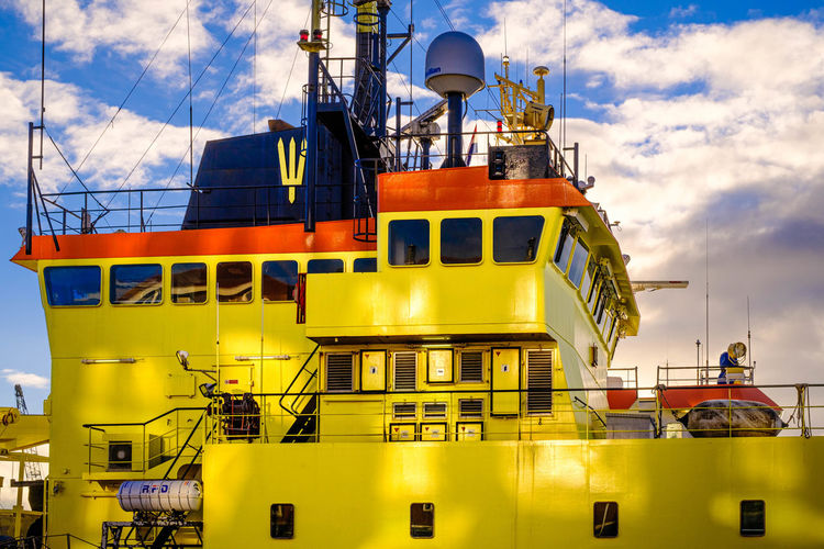 Low angle view of yellow ship against sky