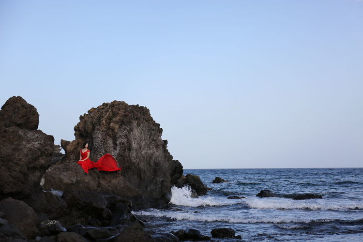 Scenic view of red cliff by sea against clear sky