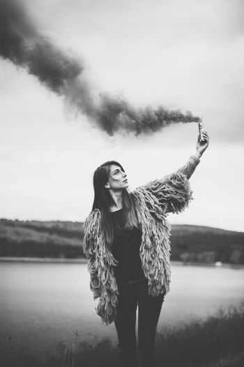 Woman holding distress flare while standing against sky