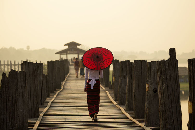 Morning time at U Bein Bridge mandalay,myanmar Boardwalk Bridge Casual Clothing Day Full Length Holding Leisure Activity Lifestyles Mandalay Myanmar One Mid Adult Man Only Outdoors Person Rear View Red Sky The Way Forward Ubeinbridge Umbrella Walking Weather Women, Wooden
