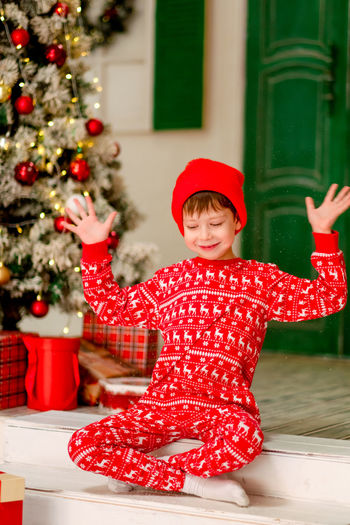 Full length of boy in christmas tree during winter