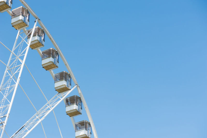 Detail of a ferris wheel against blue sky Ferris Wheel Ferriswheel Amusement Park Amusement Park Ride Architecture Arts Culture And Entertainment Blue Blue Sky Built Structure Clear Sky Copy Space Day Low Angle View No People Outdoors Sky
