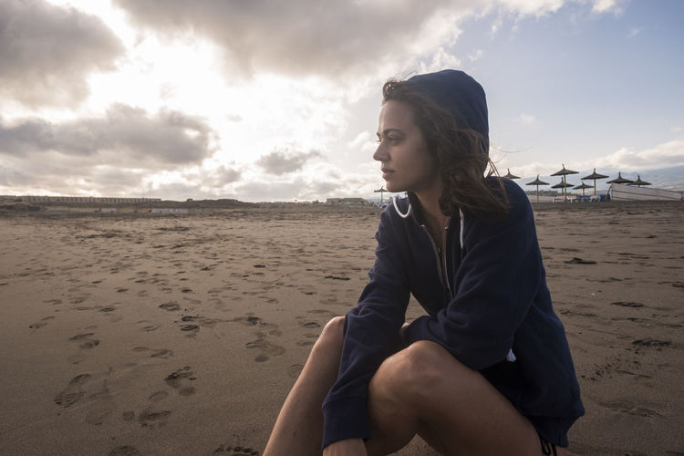 Young woman looking away while sitting at beach