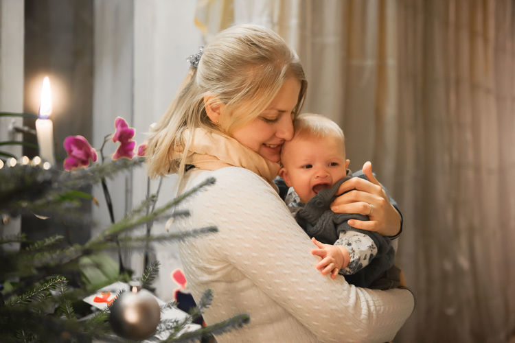 Side View Of Mother Carrying Baby Girl By Christmas Tree At Home