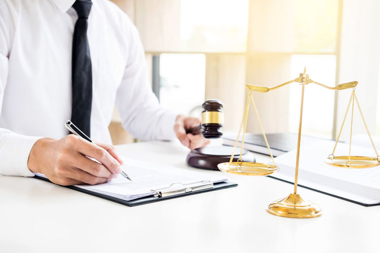 Midsection Of Lawyer Reading Documents While Sitting At Desk In Office
