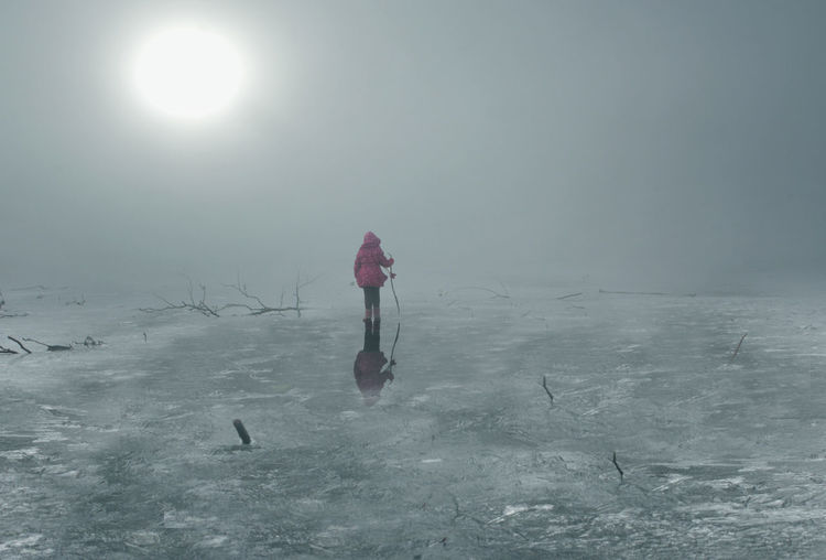 Rear view of woman standing on frozen lake against clear sky