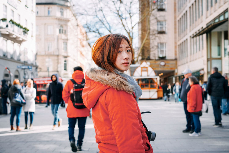 Portrait of woman standing on footpath in city during winter