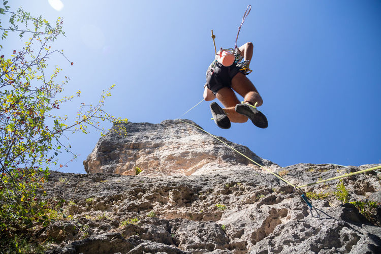 Low angle view of man rock climbing against sky