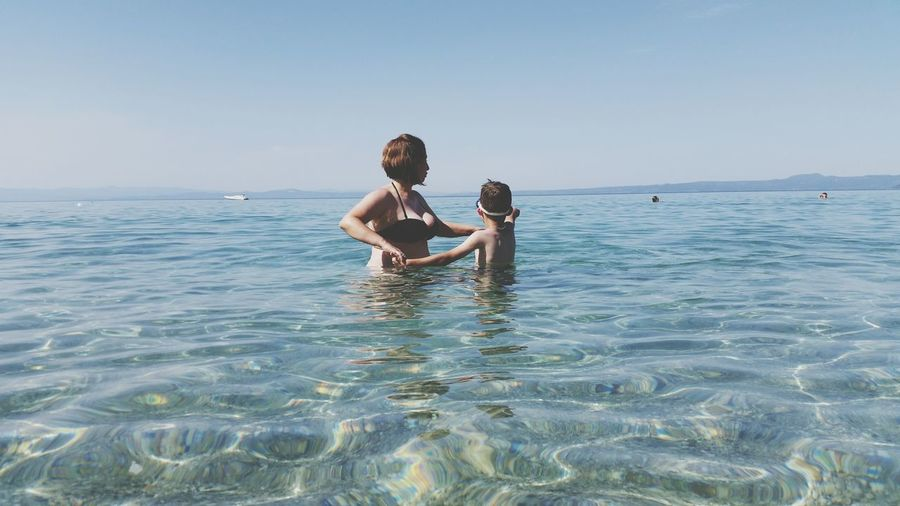 EyeEm Selects Water Sea Child Swimming Togetherness Beach Happiness Smiling Summer Shirtless Beach Holiday Single Parent Ankle Deep In Water Swimming Trunks
