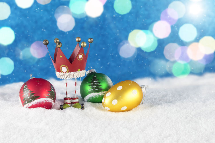 Group of Christmas decoration composed of colorful baubles and red crown figurine on white snow and shiny blurry blue background. Advent Baubles Celebration Christmas Christmas Figures Copy Space Holidays Postcard Shiny Winter Xmas Xmas Decorations Background Blank Space Christmas Decoration Christmas Decorations Christmas Figurine Colorful Decorate Decoration Greeting Card  Ornaments Snow Wallpaper