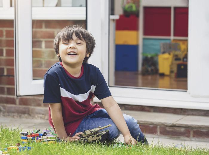 Smiling boy sitting in yard