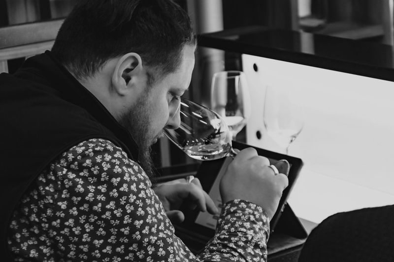 Close-up of man drinking wine in restaurant