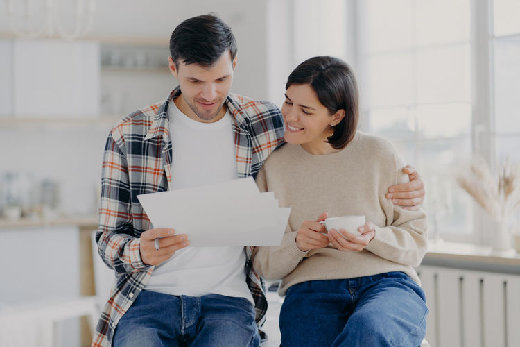 Couple reading documents while sitting at home