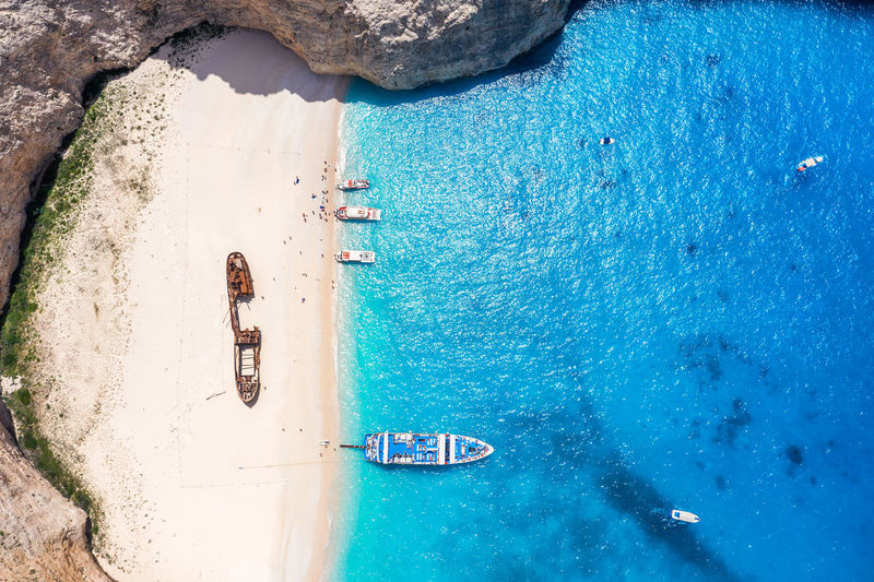 Aerial view of shipwreck at beach and boat in sea