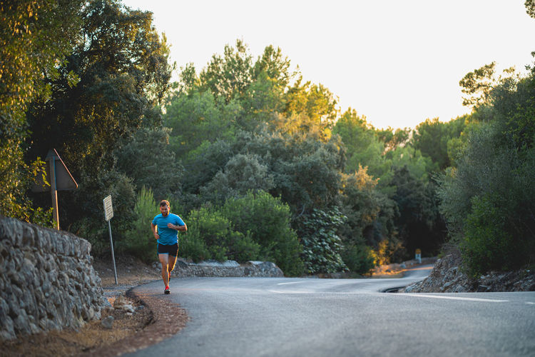 Man running on road amidst trees against clear sky