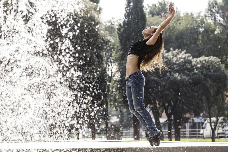 Full length of woman dancing against trees