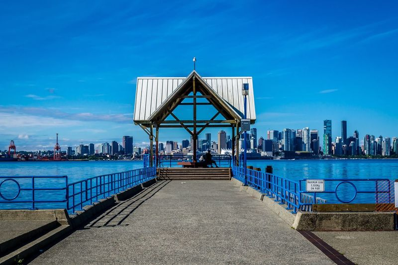 Jetty at riverside with city skyline in background
