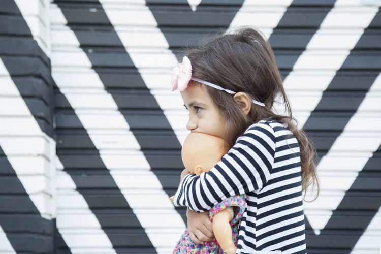 Cute girl looking away while holding doll against wall