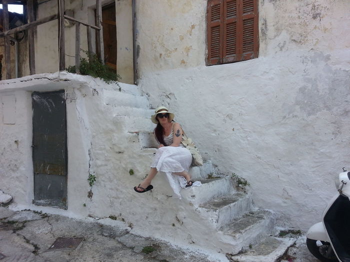 Young woman sitting on steps outside old house
