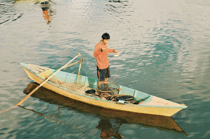High angle view of fisherman standing in boat on lake