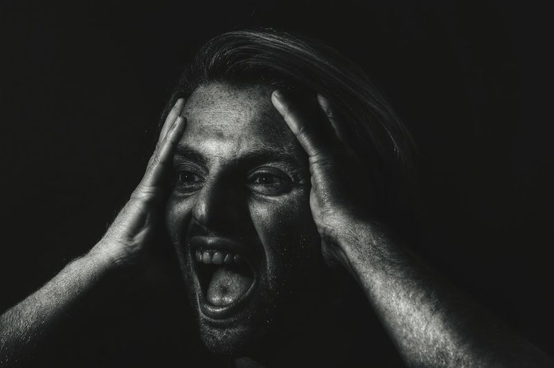 Young Woman Screaming Over Black Background