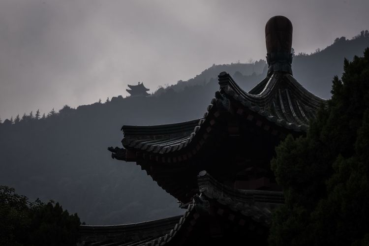 Low angle view of temple and building against sky
