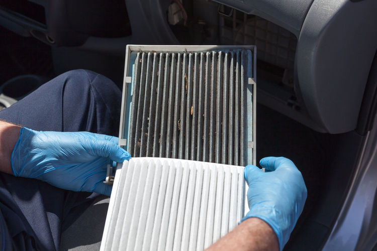 Cropped hands of man holding car air filter