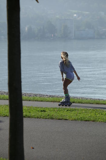 Woman rollerblading Roller Beauty In Nature Blade Day Full Length Grass Leisure Activity Lifestyles Nature One Person Outdoors People Real People Rollerblade Rollerblades Rollerblading Skate Skating Sky Standing Water Women Young Adult Young Women