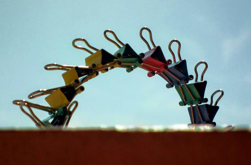 Colorful paper clips against sky