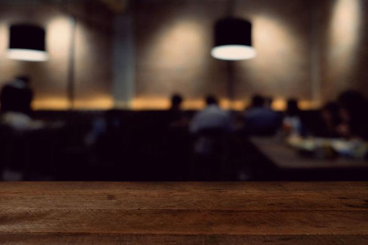 Defocused image of people sitting on illuminated table