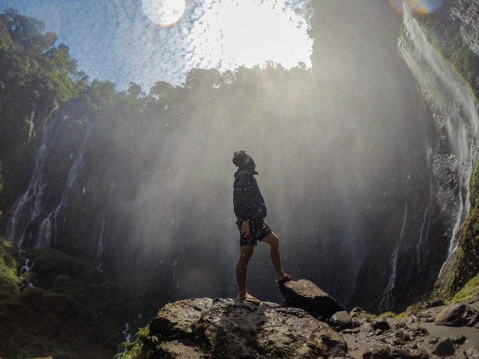 Low angle of man looking away standing by waterfall