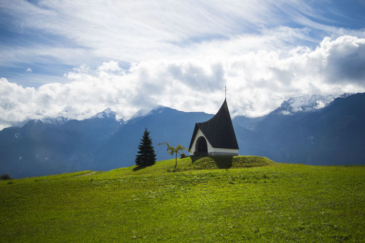 Chapel on green hill against mountains